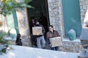 Los agentes salen de la casa de Ángel de Cabo con cajas llenas de documentación.