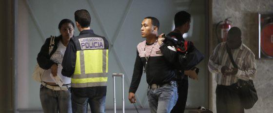 Un policía con viajeros llegados al aeropuerto de Barajas.