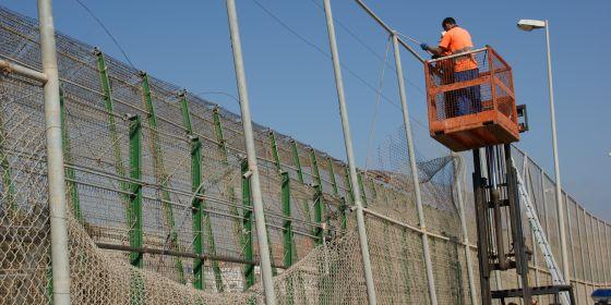 Dos operarios reparan un fragmento de valla arrancado en Melilla.