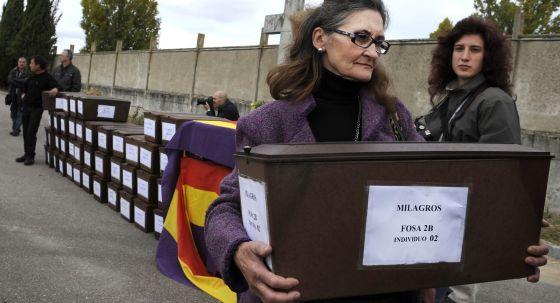 Maria Caridad Delgado lleva un cofre con los restos de una persona fusilada.