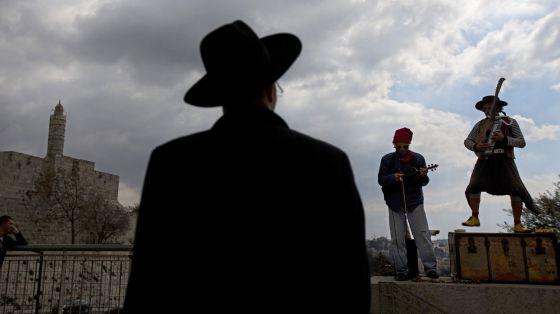 Un judío ultraortodoxo observa una actuación musical callejera frente a la Torre de David en el casco antiguo de Jerusalén.