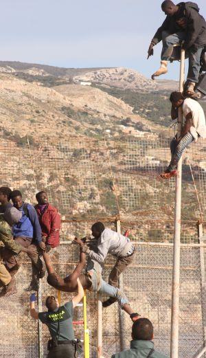 Algunos de los inmigrantes encaramados a la valla de Melilla.