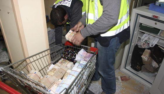 Agentes policiales con parte del dinero intervenido en la 'operación Emperador' contra el blanqueo de capitales.