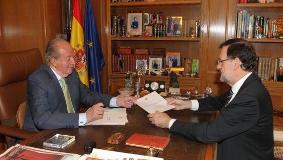 El rey Juan Carlos I entrega a Rajoy el documento de abdicación.