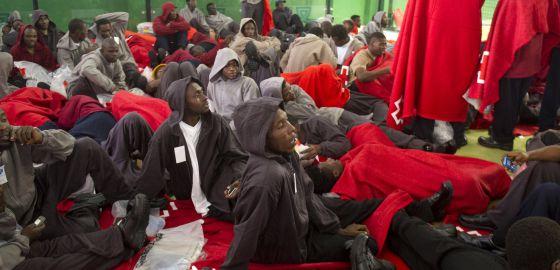 Inmigrantes descansan dentro de un centro deportivo en Tarifa, este martes.