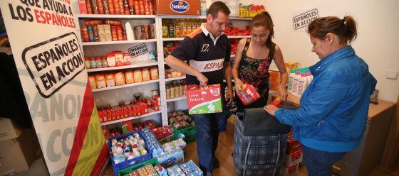 Una mujer recoge alimentos donados por Españoles en Acción, una ONG nacionalista, en Alcalá de Henares.