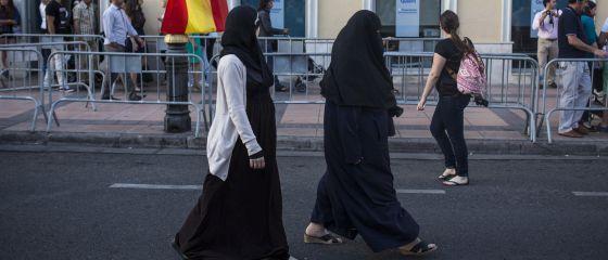 Mujeres musulmanas caminan por la Avenida Rey Juan Carlos I de Melilla, al acabar un desfile militar el pasado junio.