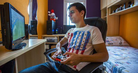 El joven gaditano José Luis Flores juega con la Play Station en su habitación.