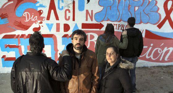 Un grupo de voluntarios de la asociación Apoyo Positivo frente a un grafiti de concienciación sobre el sida en el centro de Madrid.