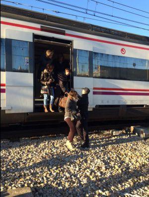 Un policía ayuda a bajar a los pasajeros del tren desalojado por amenaza de bomba.