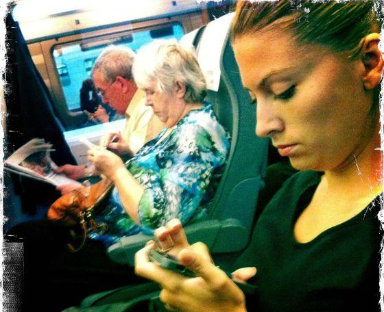 Una mujer lee el movil en el tren.