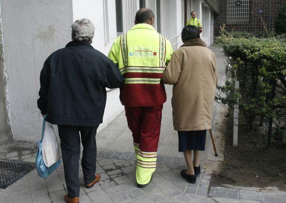 Un asistente acompaña a dos pacientes de diálisis en Madrid.