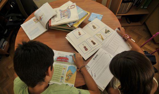 Alumnos en clase consultando sus libros de texto.