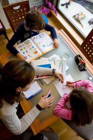 Una madre ayuda a sus hijos con los deberes.