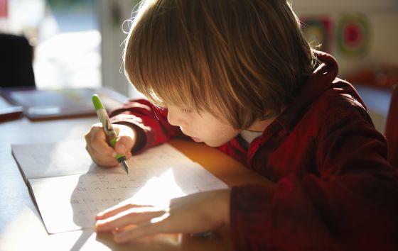 Un niño, haciendo los deberes.