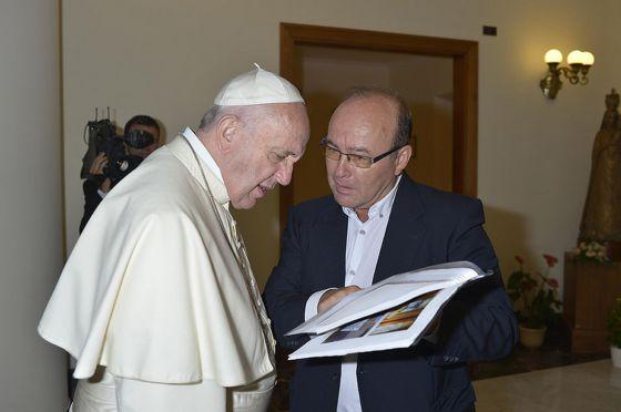 Francisco y Vidal hojean el libro con los artículos del Papa y, después, el dossier MCSPA.
