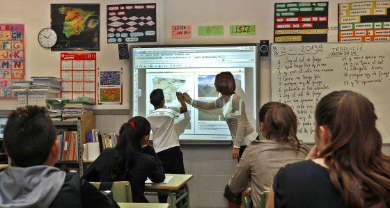 Una profesora imparte clase con una pizarra digital