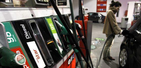 Una mujer pone combustible a su vehículo.