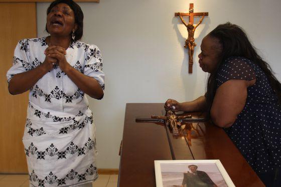 La madre de Samba Martine (izquierda), durante su entierro.