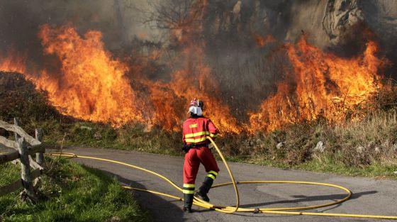 Un bombero apaga un incendio en Ribera de Arriba (Asturias), este lunes.