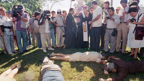 Un arzobispo y un grupo de periodistas junto a los cuerpos, en 1989.