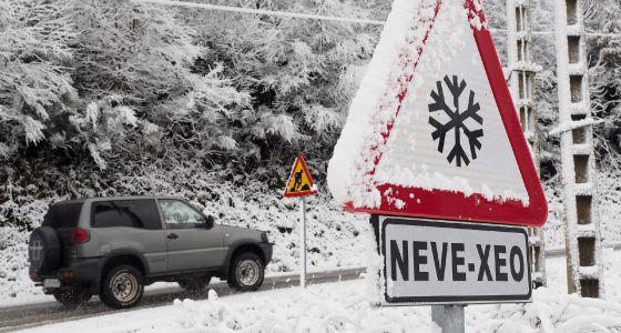 Un automóvil circula por una carretera nevada de Galicia.