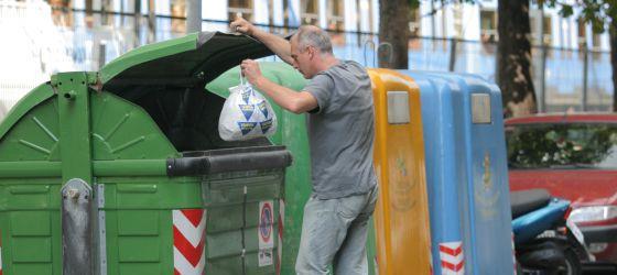 Una persona deposita una bolsa de basura en un contenedor en San Sebastián.