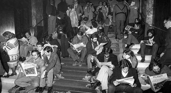 Varios periodistas leen EL PAÍS en la noche del golpe de Estado fallido del 23-F, en las escaleras del hotel Palace.