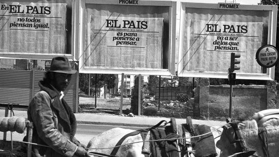 Un hombre pasa por delante de varios carteles de publicidad de EL PAÍS, en 1976.