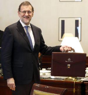 El presidente del Gobierno en funciones, Mariano Rajoy, posa con su maletín oficial tras formalizar su acta como diputado.