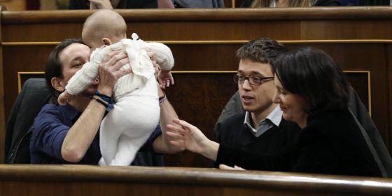 El líder de Podemos, Pablo Iglesias, coge a la hija de la diputada de su partido Carolina Bescansa, en presencia del diputado íñigo Errejón.