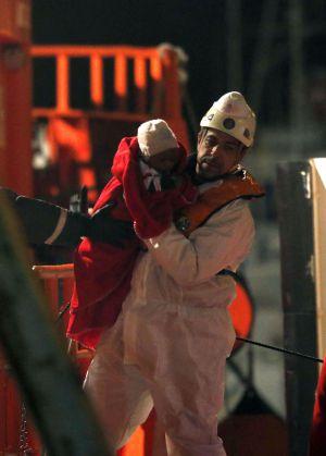 Un miembro de los equipos de emergencias traslada al bebé rescatado esta madrugada en el Mediterráneo.