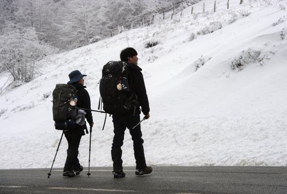 Dos peregrinos llegan al alto de Ibañeta en Navarra.