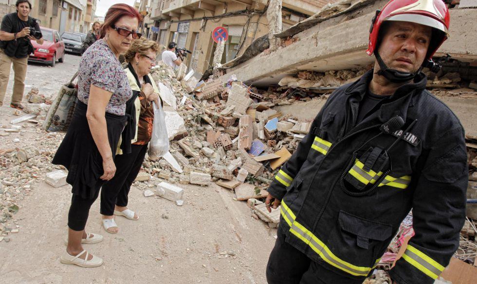 Un bombero y varios vecinos ante las ruinas de un edificio de Lorca.