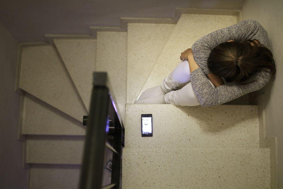 Una adolescente junto a su teléfono móvil.