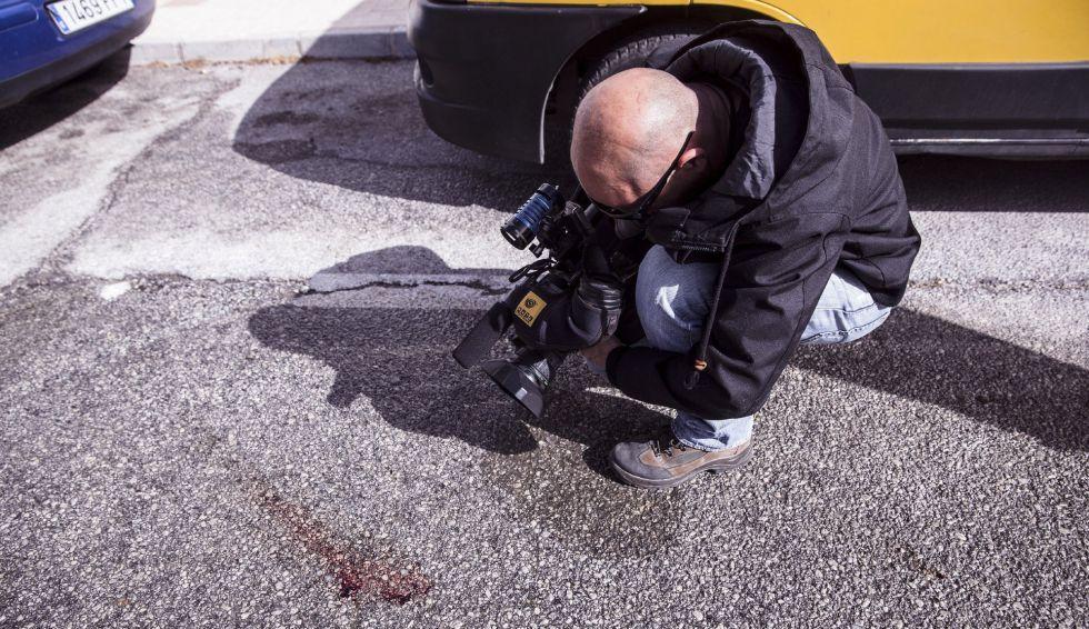 Un reportero de televisión toma imágenes de los restos de sangre del expolicía apuñalado por la espalda en Torremolinos.