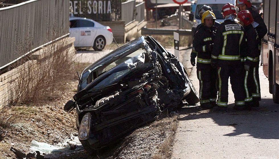 Un equipo de bomberos junto a un vehículo siniestrado en Soria.
