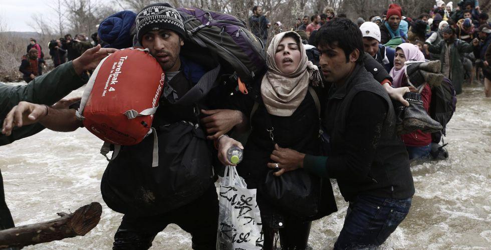 Refugiados intentan cruzar la frontera entre Grecia y Macedonia.