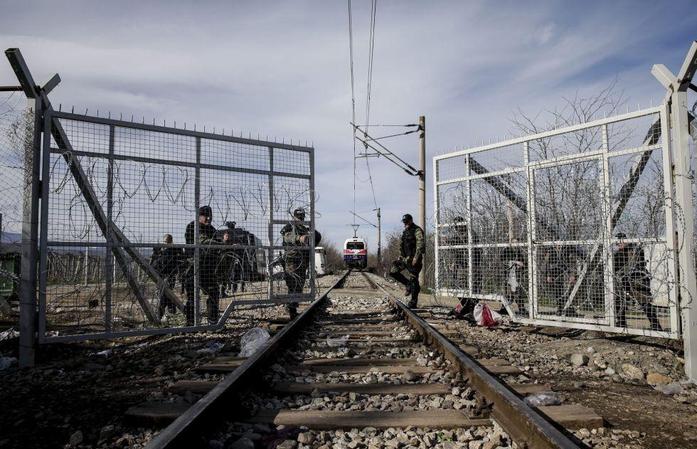 Policías macedonios abren la puerta que separa la frontera para que pase un tren, junto al campamento de refugiados de Idomeni, el 8 de marzo del 2016.