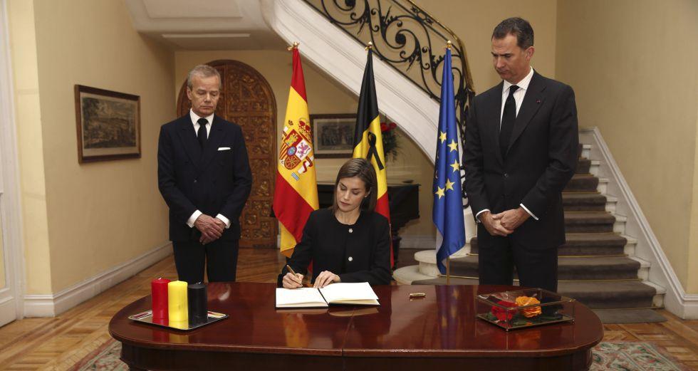 La reina Letizia, en presencia del Rey y el embajador de Bégica, Pierre Labouverie, firma en el libro de condolencias en la residencia del embajador.