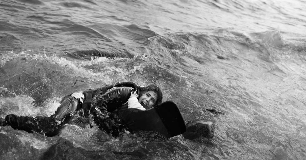 Una madre abrazada a su hijo en el agua en la costa de Lesbos.