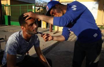 Un refigiado sirio afeita a un compañero en las puertas del CETI de Melilla