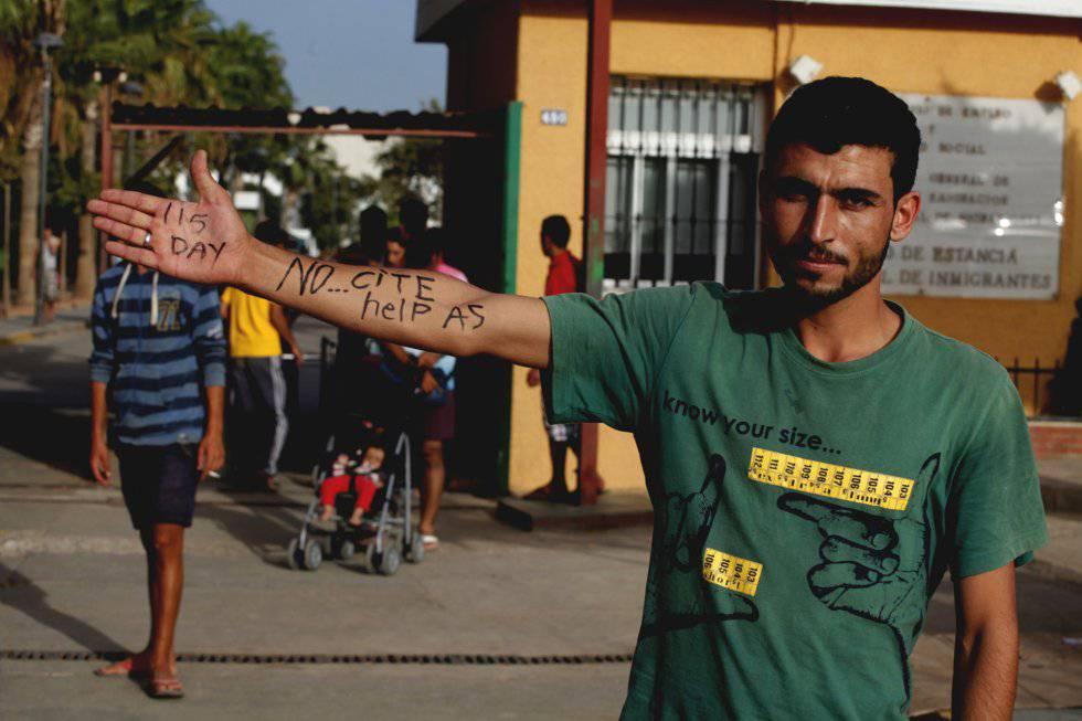 Un ciudadano sririo residente en el CETI de Melilla escribe en su brazo pidiendo ayuda.