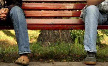 Un hombre y una mujer, sentados de forma separada en un banco.