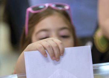 Una niña intenta introducir el sobre en la urna con el voto de su madre en Sevilla.