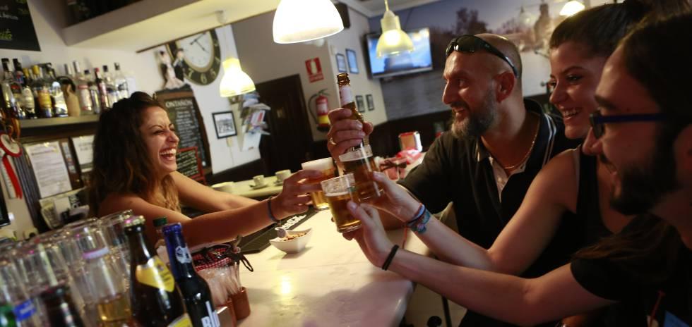 Una camarera y varios clientes de un bar de Madrid.