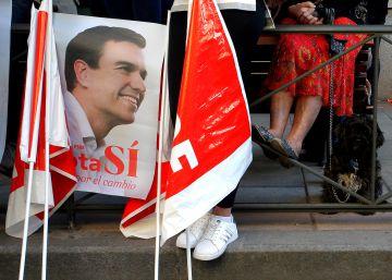 Banderas y un cartel de Pedro Sánchez junto a la sede del PSOE.