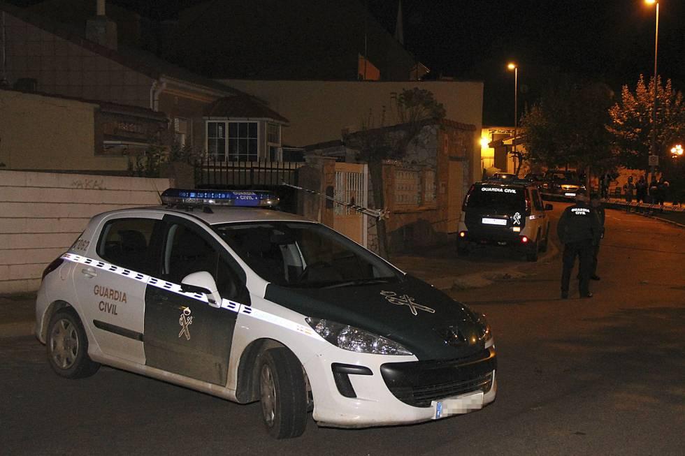 Un coche de la Guardia Civil junto a la vienda donde han sido hallados los cadáveres de un hombre y una mujer.