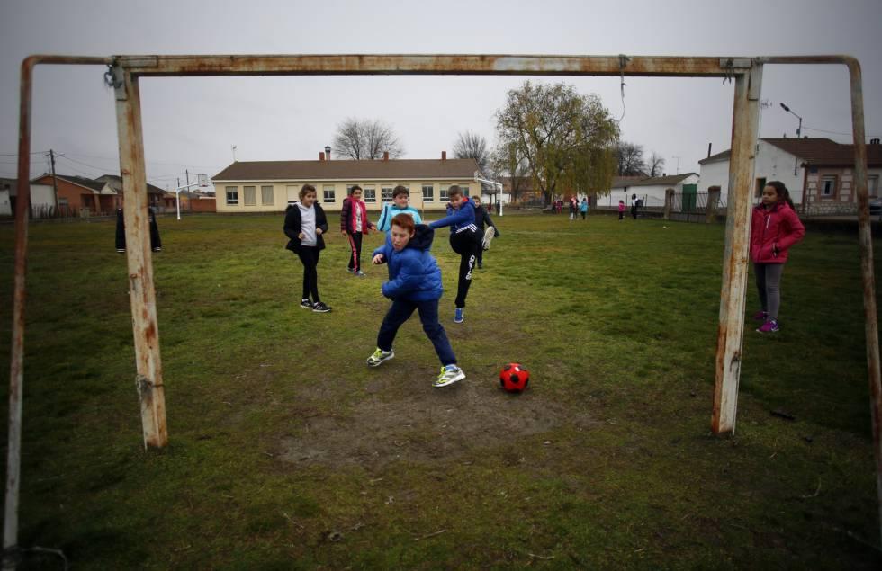Los alumnos de primaria juegan al fútbol durante el recreo.