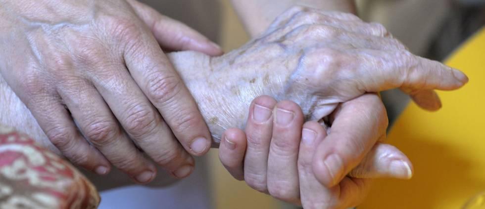 Una persona atiende a otra anciana.